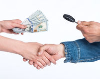 Car selling concept. Male hand holding a car key. Woman holding dollars Stock Image
