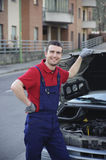 Car service. Smiling mechanic during a car service on the road Stock Image