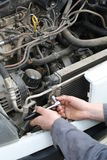 Car service. Mechanic hands with tool working on a car Royalty Free Stock Photo