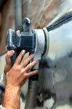 Car service, auto mechanic using a power buffer machine Royalty Free Stock Photos