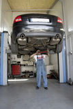 Automotive service. Auto mechanic working under car Royalty Free Stock Photo