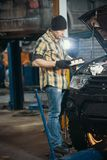 Car service. Brutal mechanic man standing by the car with open hood and holding something royalty free stock photos