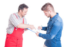 Car service client signing document on clipboard with mechanic Royalty Free Stock Photos