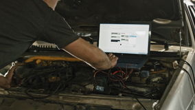 Car service, computer diagnostics: mechanic repairs the damage using the pc under the hood in car service, slider stock footage