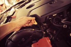 Mechanic Examining Car Engine At Repair Shop. Car service engine repair check up maintenance auto mechanic man tightened valve under hood car people hand fixing Royalty Free Stock Photos