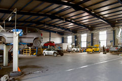 Car service garage. Auto garage repair with many cars for service Royalty Free Stock Image