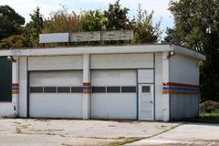 Car service garage abandoned by owners after going out of business with broken neon signs on top and dilapidated facade surrounded. With cracked concrete and royalty free stock image