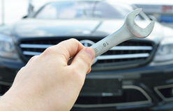 Car service. Hand holding a screw key . Stock Images