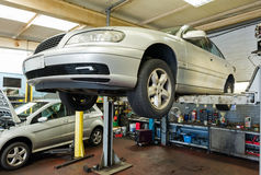 Car on a service lift. Car inspection on a service lift in a garage royalty free stock images