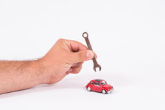 Car service. Man hand repairing red small car isolated on white, concept of car service Royalty Free Stock Photos