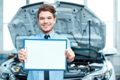 Car service manager posing with a clipboard Royalty Free Stock Photos