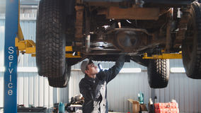 Car service - a mechanic checks the suspension of SUV, wide angle. Horizontal stock images