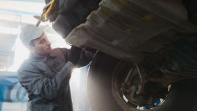 Car service - a mechanic checks the wheel of SUV, wide angle, backlight Royalty Free Stock Image