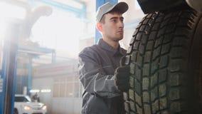 Car service - a mechanic checks the wheel of SUV, wide angle Royalty Free Stock Photo