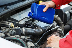 Car service. Mechanic servicing a car in a service station. Changing oil Stock Images