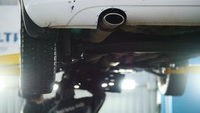 Car service - mechanic unscrewing automobile device while working under a lifted car, exhaust pipe. Close up stock video footage