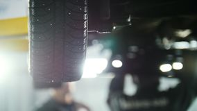 Car service - mechanic unscrewing automobile device while working under a lifted car, wheel. Close up stock video