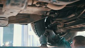 Car service - mechanic unscrewing automobile parts while working under a lifted auto. Car service - mechanic unscrewing automobile parts while working under a stock video footage
