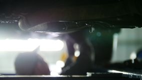 Car service - mechanic unscrewing automobile parts while working under a lifted auto, defocused background. Car service - mechanic unscrewing automobile parts stock video footage