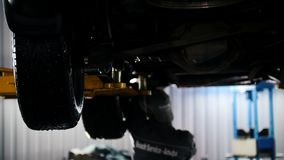 Car service - mechanic unscrewing automobile parts while working under a lifted car. Backlight stock footage