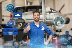Happy auto mechanic man or smith at car workshop. Car service, repair, maintenance, gesture and people concept - happy smiling auto mechanic man or smith showing Stock Photography