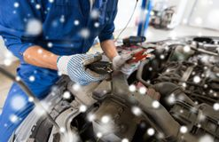 Auto mechanic hands with cleats charging battery Royalty Free Stock Photos