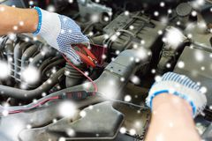 Auto mechanic hands with cleats charging battery Royalty Free Stock Photo