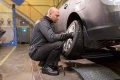 Auto mechanic changing car tire at workshop Royalty Free Stock Photos