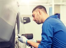 Mechanic with screwdriver changing car tire royalty free stock images