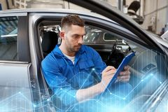 Auto mechanic man with clipboard at car workshop. Car service, repair, maintenance and people concept - auto mechanic man or smith with clipboard writing at Royalty Free Stock Photo