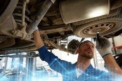 Mechanic man with flashlight repairing car at shop Royalty Free Stock Photos