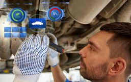 Mechanic man with flashlight repairing car at shop Royalty Free Stock Photo