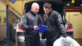 Auto mechanics with car tire at workshop. Car service, repair, maintenance and people concept - two auto mechanics with tire and clipboard talking at workshop stock footage