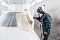 Car service station. Worker painting a white car in special garage, wearing costume and protective gear.  royalty free stock photography