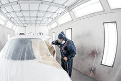 Car service station. Worker painting a white car in special garage, wearing costume and protective gear.  royalty free stock photos