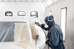 Car service station. Worker painting a white car in special garage, wearing costume and protective gear.  stock photos