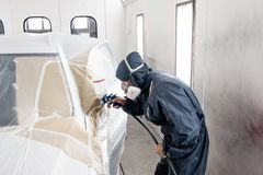 Car service station. Worker painting a white car in special garage, wearing costume and protective gear.  stock images
