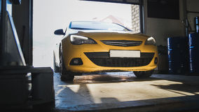 Car service work - yellow car drives to garage Royalty Free Stock Photo