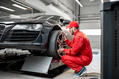 Car service worker changing wheel. Car service worker in red uniform changing wheel of a sport car at the tire mounting service stock images