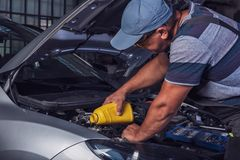 Car service worker diagnoses car breakdown stock images