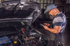 Car service worker diagnoses car breakdown stock photography
