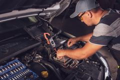 Car service worker diagnoses car breakdown royalty free stock photography