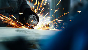 Car service - worker grinding metal construction with a circular saw. Telephoto Royalty Free Stock Image