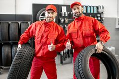 Car service workers with new tires at the shop. Portrait of a two car service workers in red uniform standing together with new tires at the store royalty free stock photo
