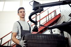 At a car service: a young and attractive guy is checking a tire at work royalty free stock image