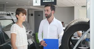 Car service, a young car manager standing next to tires and discussing something with a client woman, she talks to a stock images