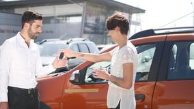 Car service, young car manager stands next automobile and discusses something with female client she talks mechanic and Royalty Free Stock Photos