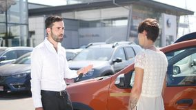 Car service, young car manager stands next automobile and discusses something with female client she talks mechanic and Royalty Free Stock Image