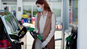 Car service, a young woman a motorist in a protective mask and gloves fuels his car at a gas station during isolation