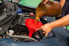 Car servicing mechanic pouring oil to engine Royalty Free Stock Image